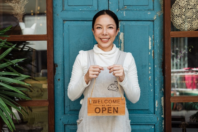 """Woman business owner holding """"open"""" sign"""